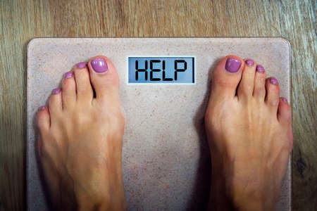 Close up of female feet standing on bathroom scale. Concept of shaping and wellness. Time to loose weight. Woman finds out that she has overweight.