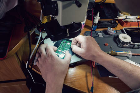 Close-up photos showing process of mobile phone repair. Phone repair under the microscope. Mobile fee. repair gadgets at home closeup. Male hands check the performance of the phone Foto de archivo - 129844293