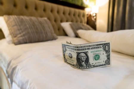 paying us money dollar on white bed in hotel. tips left on the bed for the maid of the hotel room. Tips at the bed for the housekeeper in hotel.