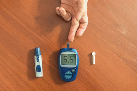 Hypoglycemic diabetic patient testing her blood for sugar level at home low blood sugar.