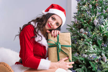 Christmas woman portrait hold christmas gift. Smiling happy girl on Christmas tree background. young woman opens a Christmas gift.