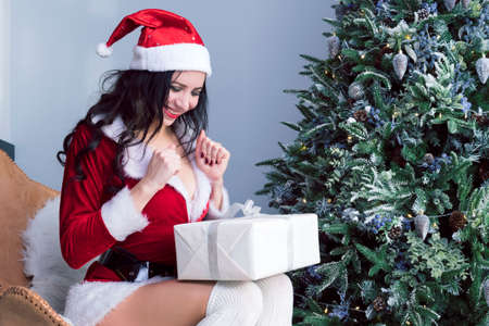 girl in a Santa costume opens a gift in anticipation, rubs his hands and claps his hands.. christmas, x-mas, winter, happiness concept - smiling woman in santa helper hat with gift box.