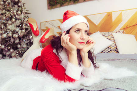young beautiful girl in a red Santa Claus suit is lying on bed and dreamily looking into the distance against background of apartment decorated for Christmas.