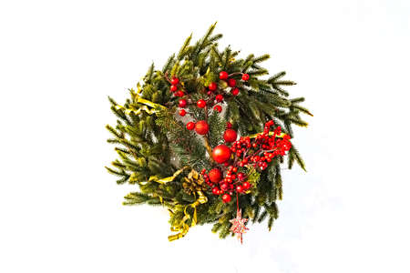 traditional green christmas wreath with holly berry isolated on white background. festive decoration, beautiful spruce wreath with red flowers, balls, berries and stars.