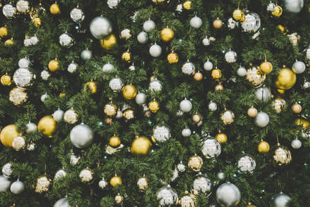 Christmas tree background, Gold and silver balls hanging on the green Christmas tree closeup