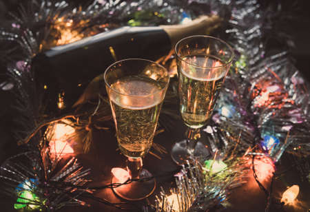 Two Glasses with champagne and bottle on a wooden table decorated Imagens - 129846573