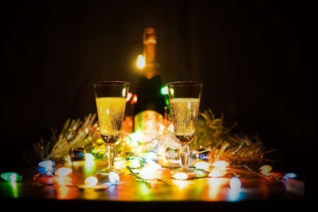 two glasses of champagne toasting against