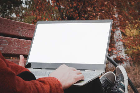 male hands holding a laptop with a touch screen and pointing at a blank white screen. Freelancer working outdoors in the Park