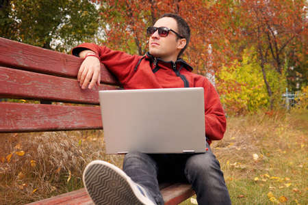 freelancer in autumn Park. Magazine editor revising new article received by email. man surfing web on a laptop connected to wifi. Student preparing for exams outdoors by using a portable computer