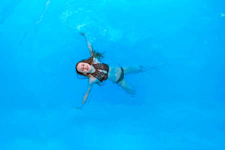 Attractive woman in a black bathing suit floating on her back in the swimming pool and relaxing, copy space. view from the top