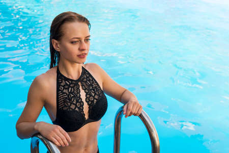 young girl comes out of the pool on the stairs. Relaxing by the pool. model posing by the water. beautiful girl in black bikini standing on ladder in swimming pool. copy space