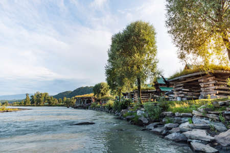 Home and garden furniture near the shore of the river. agrotourism Foto de archivo - 131278814