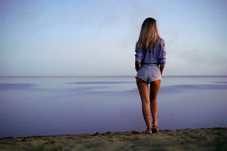 a young beautiful sexy girl stands on the lake and looks into the distance at the horizon in evening. rear view. Beautiful serene nature. minimalism. blonde walks on the sand. copy space Foto de archivo - 131278902