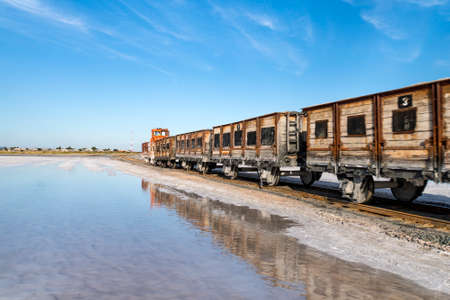 Old train rides on the railway laid in the water through the salt lake. train travels from water. Mined salt in Lake Burlin. Altai. Russia. Bursolith.