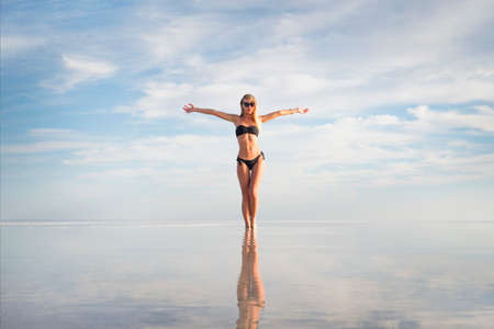 Young adult woman in black white swimsuit standing in water at water texture. Cute sexual girl on summer lake background. hands to side. Low white clouds reflected in clear water. Bolivia Uyuni Foto de archivo - 131278992