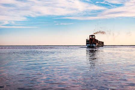 Der Zug schwimmt auf dem Wasser gegen den blauen Himmel. Salzindustrie, Salzbergbau.