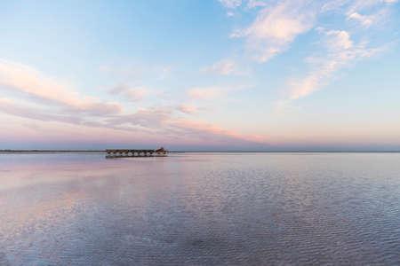 Trainieren Sie mit abgebauten Salzfahrten auf der Wasseroberfläche vor dem Hintergrund eines wunderschönen Sonnenuntergangs. Salt Lake Bursol, Burlinskoye-Dorf. Altai-Gebiet. Russland. Standard-Bild