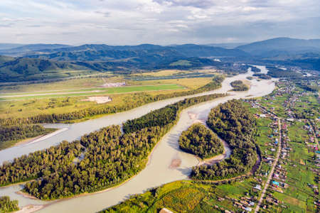 Aerial view of Katun river, in Altai mountains. Top view of the mountain river in the Altai mountains and the village of Aya. Altai territory. Foto de archivo - 131279106