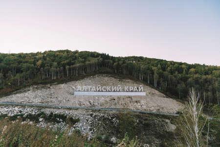 Inscription in Russian language Altai Krai is the name of a region in Western Siberia in Russia. Letters on a rock near the serpentine road. tourist cluster Belokurikha 2 Foto de archivo - 131279193