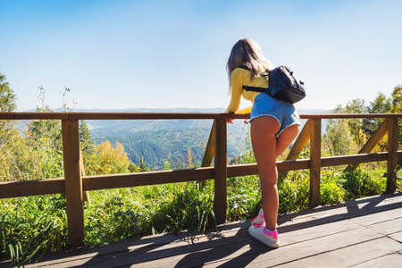 A young girl looks at the beautiful nature. The view from the back. to enjoy the scenery. Sexy woman in short shorts on a bridge in the mountains. Country walks in the countryside