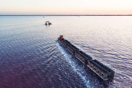 Awesome train rides on the rail in the water with white salt on the background of beautiful blue sky. aerial view, view from the top Foto de archivo - 131279239