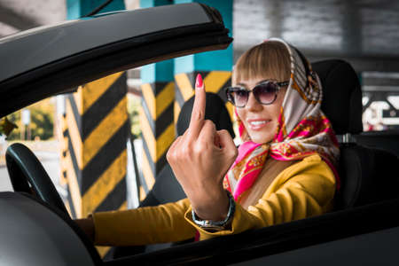 Pretty lady sitting in her car and showing middle finger. Business lady demonstrating you off sign from open window. Fashionable stylish rich successful woman handkerchief in cabriolet.
