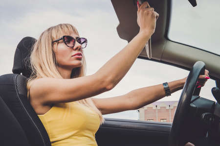 a woman admires her beauty in the reflection. Young cheerful woman driving car. Blonde girl looks in the mirror and preens. woman lowers the sun visor holding the steering wheel