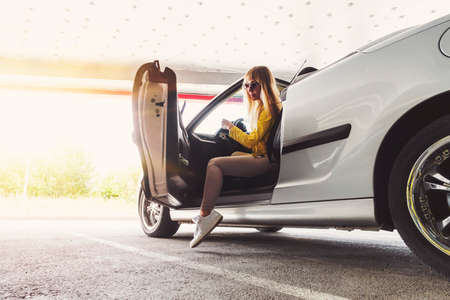 To get rich. Beautiful successful gorgeous girl sitting in the convertible cabrio car on the warm sunny day in a city. Business lady gets out of the car in the underground garage.