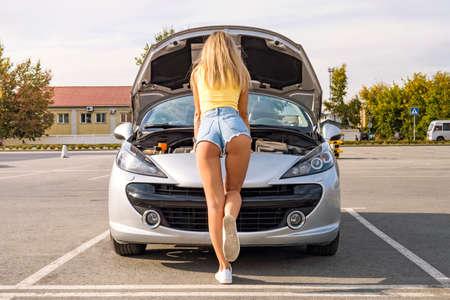 abre el capó del coche gris. Foto de la parte de atrás de la niña en pantalones cortos remendando el coche en la calle Aparcamiento en la ciudad en día de verano