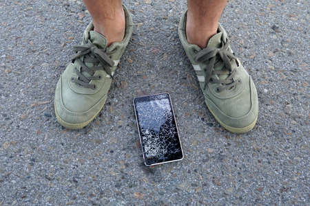 Smartphone fell on a street. Broken mobile phone. cellphone fell out of my pocket. guy found a broken phone.