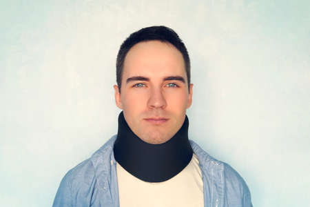 Man with neck brace after whiplash injury blue background, black neck collar on male patient. treatment of diseases of the neck and blood vessels of the brain.