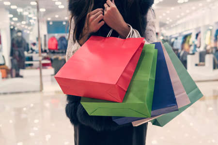Half lenght shot of a girl holding many shopping paper bags at shopping area background. Young girl pressing heap of bags to breast in mall. Lady carrying packages with purchases. Woman buys up much Banco de Imagens