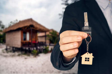 man buying new house. hand receiving house key. Close up hand holding house key. Rent a Bungalow on the beach for a holiday. Standard-Bild