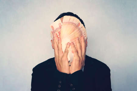 close-up view of man holding russian rubles banknotes in hand. 5000 banknotes folded fan cover the face of the businessman. young successful man washes his face with money.