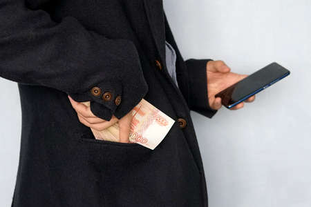 young man holds the money in his hand and presses the screen of the smartphone. Earns money through the mobile app. Business via smartphone. Archivio Fotografico