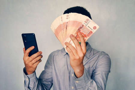 young man holds the money in his hand and presses the screen of the smartphone. Earns money through the mobile app. Business via smartphone. Фото со стока