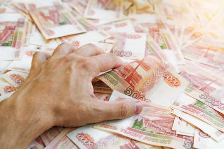 Lust for money. Large stack of banknotes, Russian rubles, banknotes 5000 rubles. hands are grabbing money.