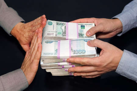 A million rubles in men's hands. Bribery in Russian rubles in a dark room. The concept of corruption and bribery. The rejection of money. honest official refuses a bribe. Фото со стока