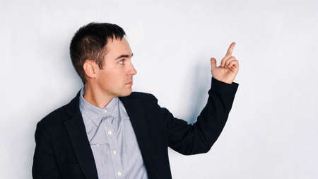 business man points with fingers in the right side. A young man in a jacket points to an empty space. a blank Form for design.