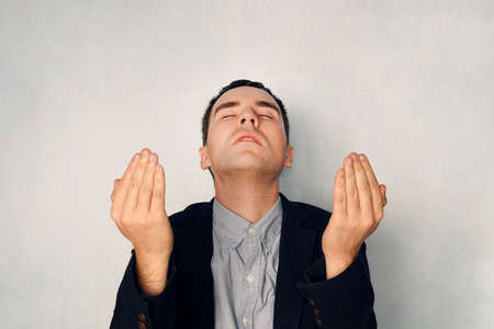businessman raised his hands in prayer. A petition for God's blessing. Prayer and meditation concept. A focused man in a business suit meditates, blue background