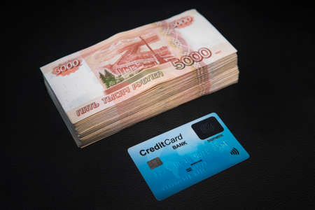 Card and russian rubles banknotes. A wad of money from Russian rubles and a plastic Bank card lie on a black background