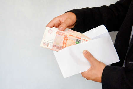Large denominations of 5000 rubles in a white envelope. A man hand holds an envelope with money. the concept of bribery and corruption. male hands recalculate salary. cash, cashflow