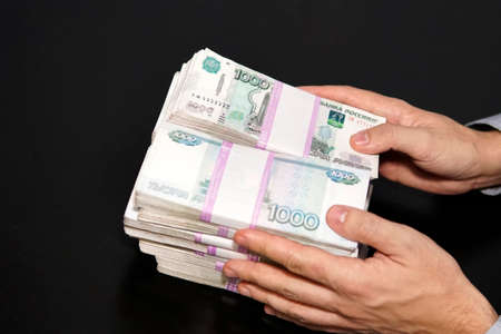 large stack of paper money in the hand of an adult businessman. The concept of financial success. a lot of money in mens hands. Give or take a bribe, corruption