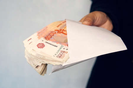 Large denominations of 5000 rubles in a white envelope. A man hand holds an envelope with money. the concept of bribery and corruption. cash, cashflow
