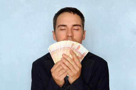 business, people and finances concept - businessman smelling Russian money. The sweet smell of money. Young guy sniffing 5000 rubles Earned money. Salary. Easy money.