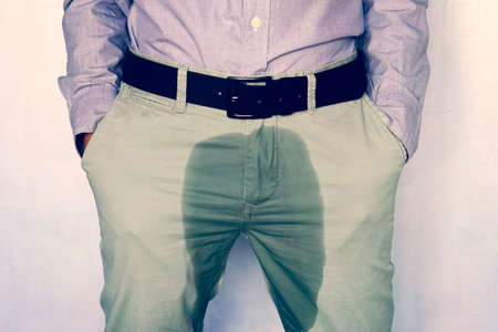 A man standing in wet pants against the wall. Urinary incontinence is an increasingly popular disease affecting younger males. incontinence and wet pants. a dark spot on a light trousers.