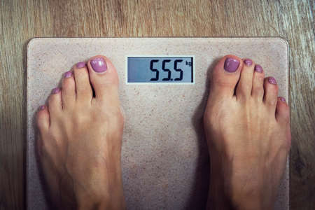 Close up of digital bathroom scale with female bare feet on it showing 55,5 kilogram on display. Woman standing on scales and viewing normal weight indication. Scale showing good shape of a girl Stock fotó
