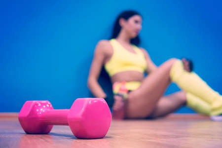 Close up of pink dumbbell lying on the gym floor at sitting sporty girl background. Concept of fitness and healthy lifestyle. Cooling down after training. Woman's workout break. Rest after exercises