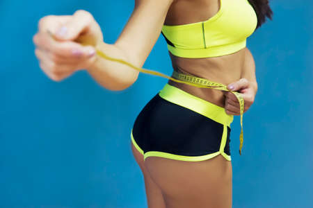 Cropped shot of girl in sportswear measuring herself with metric tape at blue background. Girl in sport top and short checking her waist size with tape. Measure of waist circumference by fit girl