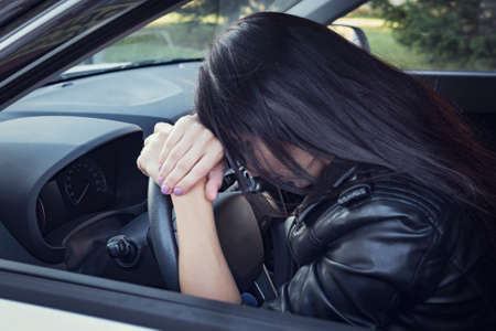 View form front window to a stressed or tired brunette girl in car lying on steering wheel. Female driver resting in vehicle. Young girl felt sleepy or sick while driving. Woman leans car wheel
